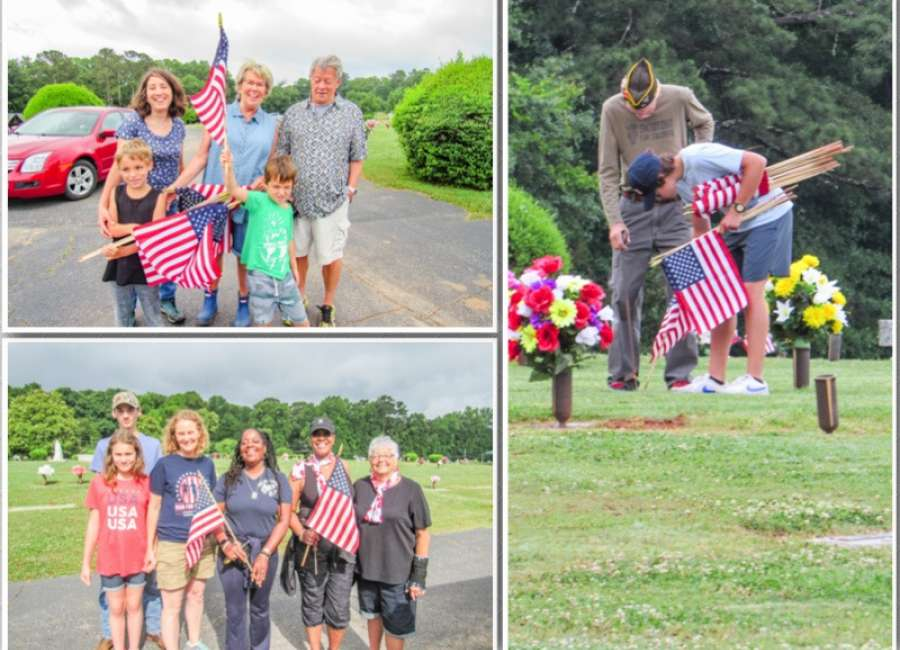 Volunteers place flags on graves of fallen