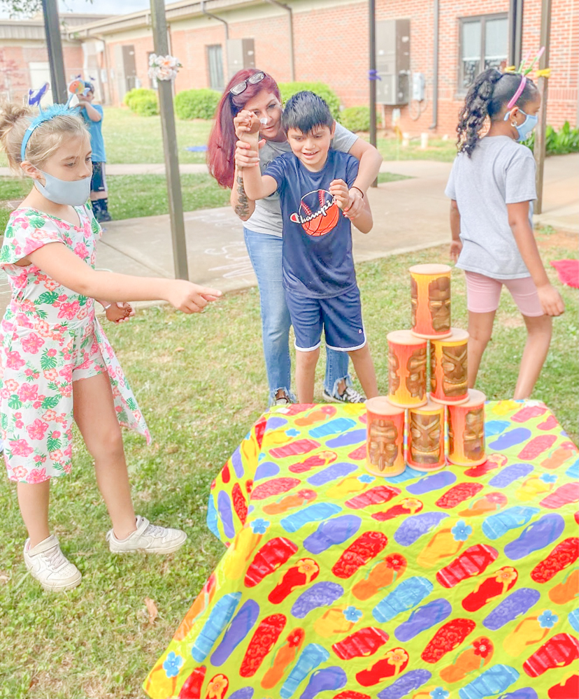Alyssa Quick, left, Kecia Sharp and Luis Aguilar-Salinas play games at the luau party for Ruth Hill Elementary School's Autism Center.